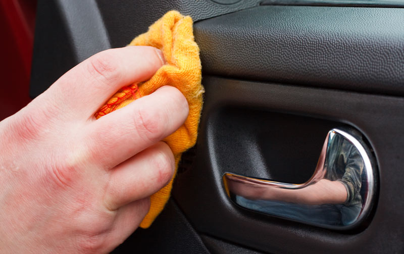 A person cleaning a car door